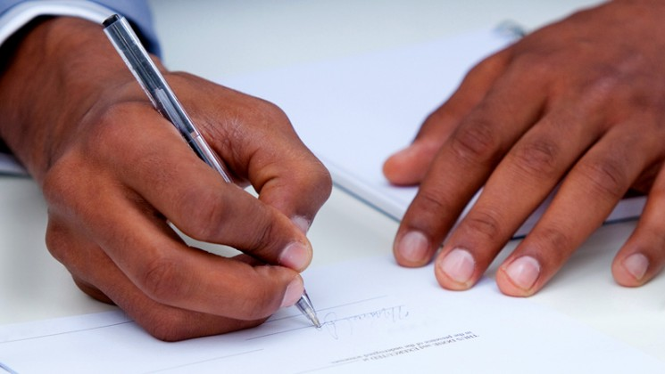 hands of a man signing a document