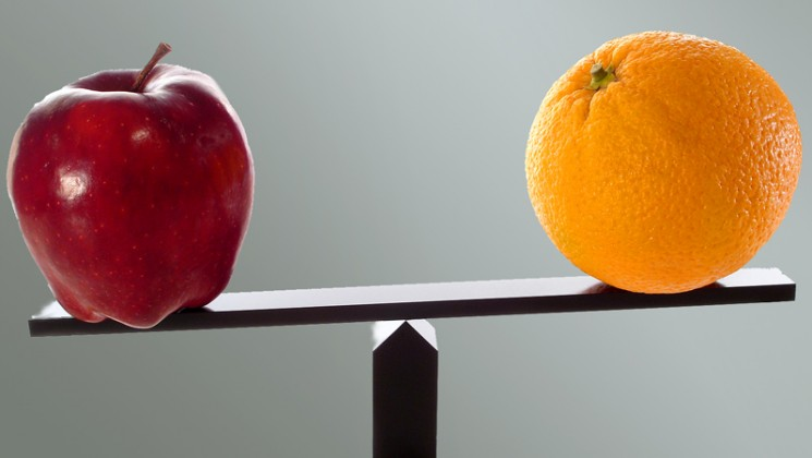 Apple and orange on scales to indicate comparison. Bigstock