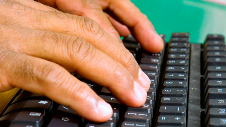 Man's hands on computer keyboard.