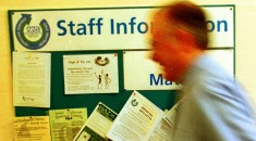 man walking past a notice board