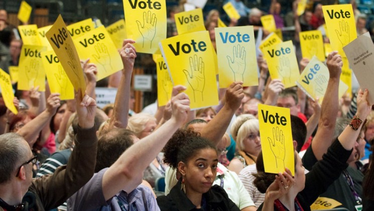 Voting cards being help aloft at a UNISON conference