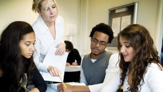 Stock image of teaching assistant helping pupils