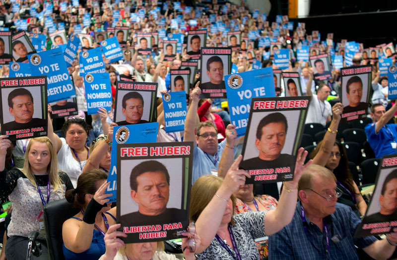 Delegates hold up photos of Huber Ballesteros in a show of solidarity. Photo: Marcus Rose / Workers' Photos