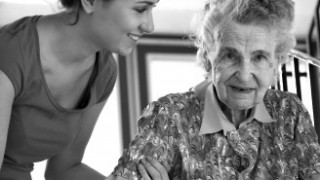 a female care worker helps an elderly woman