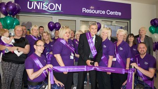 Dave Prentis cuts ribbon in front of resource centre, surrounded by members