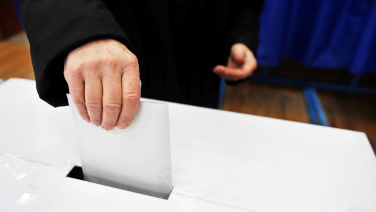 Hand of a man putting his vote in the ballot box