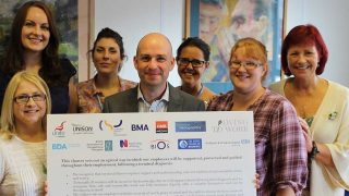 John Flannery and fellow trade unionists pose with large cardboard version of Dying to Work charter