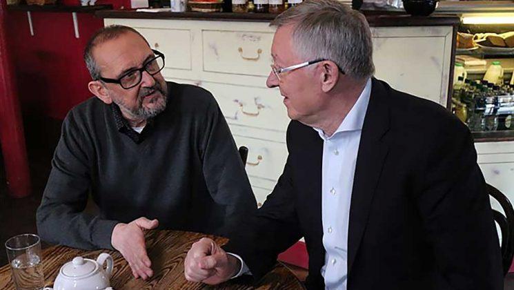 Tom Hart and Sir Alex Ferguson sitting talking in a cafe