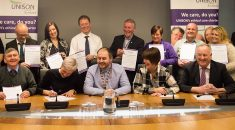 council and union representatives gather at desk and signing the charter