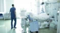 Walking medical person in hospital ward blurred background.