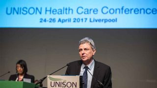 Dave Prenits at the rostrum speaking to UNISON health delegates in Liverpool