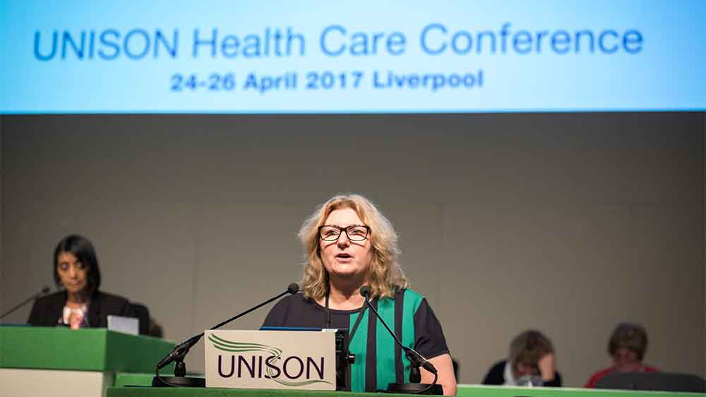 Roz Norman speaking at podium, in front of backdrop reading UNISON Health Care Conference