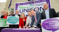 UNISON and Swansea Labour group leader sign the charter in front of a UNISON Cymru / Wales banner