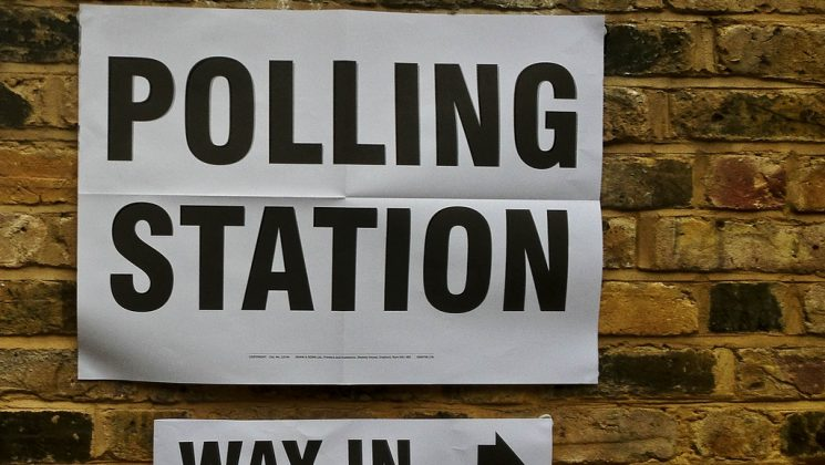 Polling station sign on a brick wall