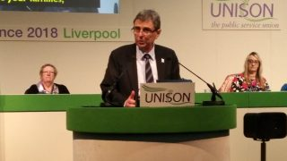 Dave Prentis stands at rostrum addressing UNISON women's conference