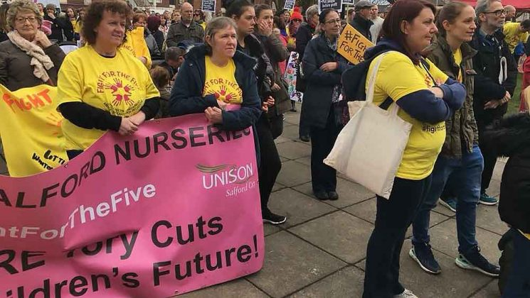 Cowd with banners at Salford nurseries rally in March
