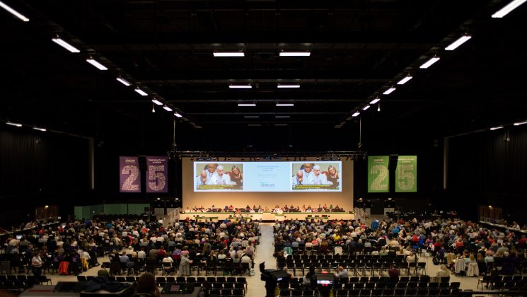 photograph of conference hall with speakers rostrum in the distance