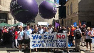 strikers on the 30 June march with placards, banner and balloons