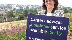 Scottish careers advice members on a hill above Fife holding a placard reading: Careers Advice – a national service provided locally