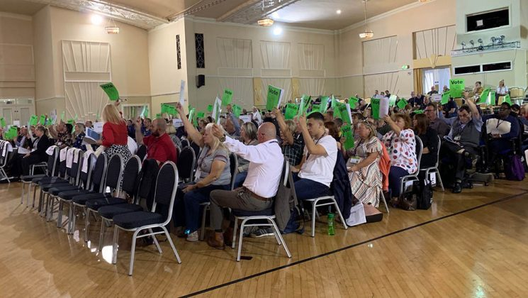 delegates holding up voting cards at the 2019 police and justice conference