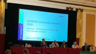 picture of platform at UNISON community seminar with Mark Drakeford speaking at rostrum
