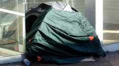 Tent of a homeless person in a commercial doorway