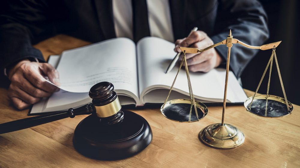 Male Lawyer Or Judge Working With Contract Papers, and Law Book