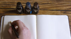 Close up of hand holding fountain pen over blank page, with ink bottle nearby