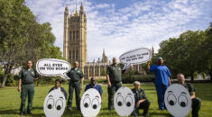 UNISON health members stand outside Parliament holding up signs that say 'All eyes on you Boris' and 'No place to hide on NHS pay'.