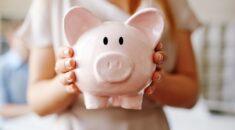 A woman holds a piggy bank